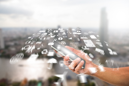 global communication: Mans hand holding smartphone with radial blurred business icon on blurred city background, communication technology concept Stock Photo
