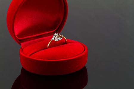 diamond shaped: Gold diamond ring in red heart shaped velvet box on dark glossy background