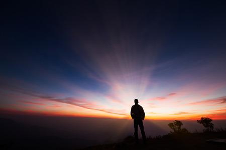 Silhouet van een mens die zich op de klip bevindt die zonsopgangachtergrond, hoop bekijkt en een droomconcept volgt