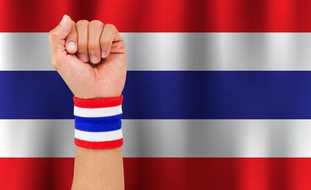 Thai national color cloth wristband on the guys wrist on waving national Thailand flag background