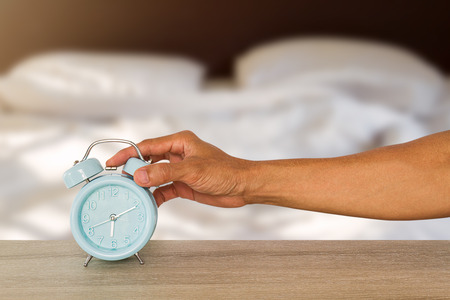 Mans hand stopping blue classic alarm clock on vintage wooden table on blurred messy white bedding background