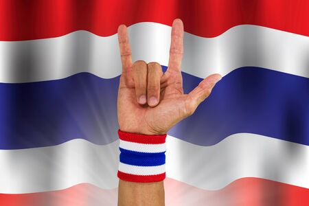 Thai national color cloth wristband on the guys wrist making I love you sign on waving national Thailand flag background Stock Photo