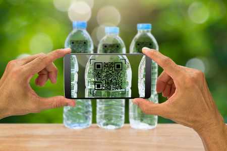 Man's hands holding smartphone scanning QR code on drinking water bottle in the garden, business concept 스톡 콘텐츠