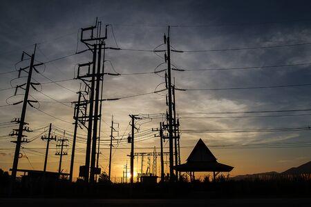 Silueta de postes de electricidad durante la puesta de sol de oro Foto de archivo - 87105520