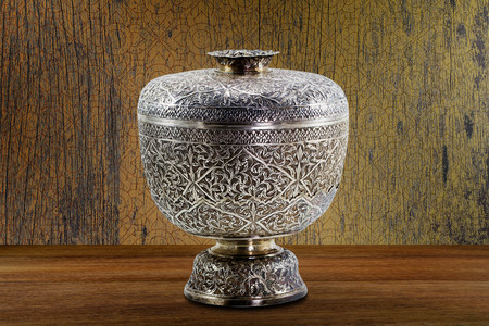 Thai antique ancient grunge silver bowl on wooden tabletop on vintage grunge wooden wall background, still life