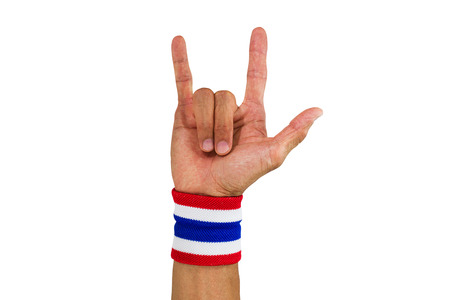 Thai national color cloth wristband on the guys wrist making I love you sign on white background