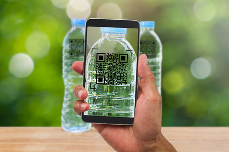 Mans hands holding smartphone scanning QR code on drinking water bottle in the garden, business concept Stock Photo