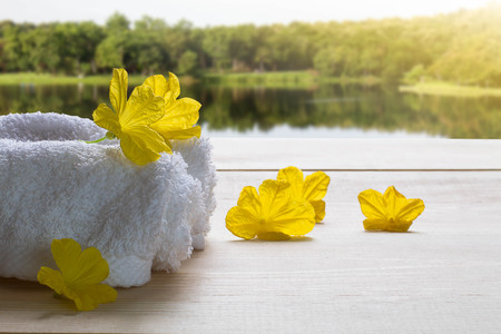white fabric texture: White towels with yellow flowers on wooden floor on blurred lake and forest background, spa concept Stock Photo