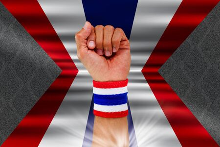 Thai national color cloth wristband on the guys wrist on waving national Thais flag on vintage Thai pattern background