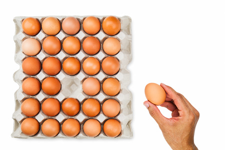 Mans hand picking up one fresh egg from paper tray, healthy eating concept Stock Photo