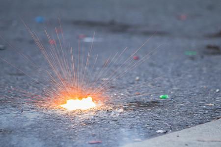 Firecracker exploding with light splash on the road during Phuket vegetarian festival