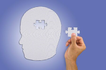 Hand inserting missing jigsaw in white mans head shape Stock Photo