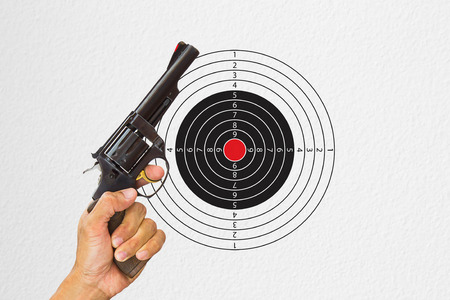 Hand holding black gun with shooting target background 스톡 콘텐츠
