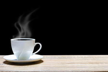 Hot cup of coffee on wooden table on dark background Stock Photo