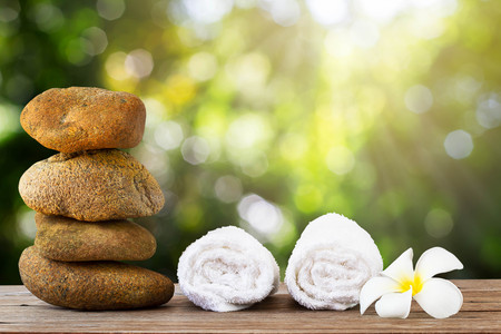 Stack of stone and white towel with flower on wooden floor on green bokeh background, spa concept