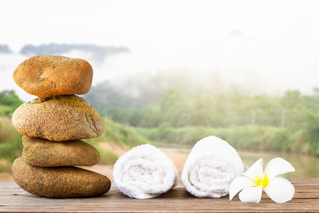 Stack of stone and white towel with white flower on wooden floor on nature background, spa concept