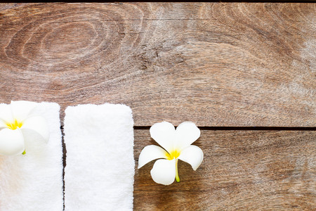 White towel with white flower on vintage wooden background, spa concept Archivio Fotografico
