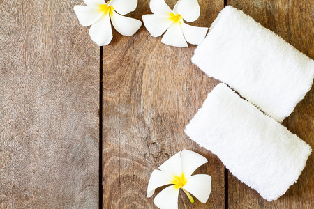 White towel with white flower on vintage wooden background, spa concept Stockfoto