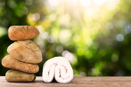 Stack of stone and white towel on wooden floor on green bokeh background, spa concept