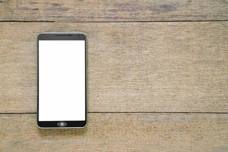 Smartphone mit weißem Bildschirm auf Vintage-Grunge-Holzhintergrund