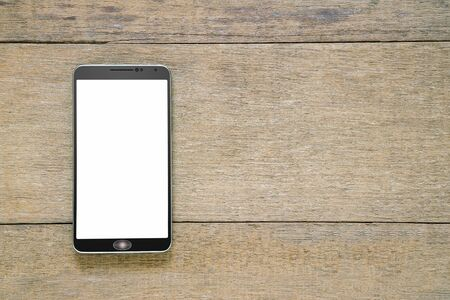 Smartphone with white screen on vintage grunge wooden background