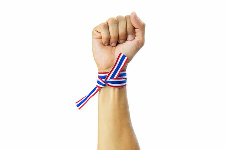 Thai national color ribbon tied up on a wrist with clenched rising fist 스톡 콘텐츠