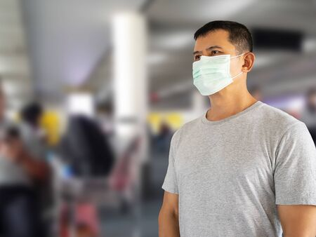 Asian man wearing hygienic face mask on blurred departure hall at airport