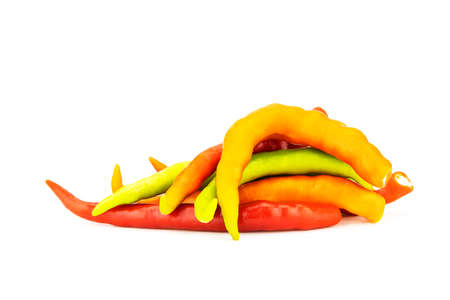 Pile of orange,yellow and green chilli isolated on white background
