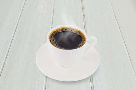 White coffee cup on white vintage wooden tabletop background