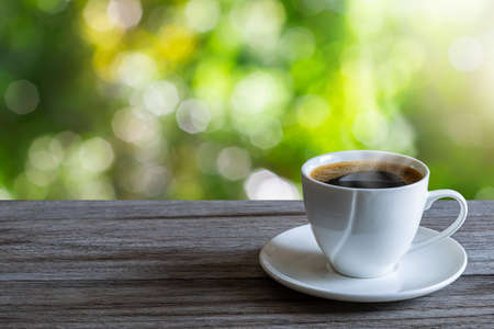 Hot white coffee cup on wooden tabletop on blurred green nature bokeh background Stock fotó - 152187237