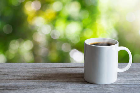 Hot white coffee cup on wooden tabletop on blurred green nature bokeh background