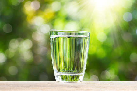 Fresh glass of drinking water on wooden tabletop on blurred green nature bokeh background Stockfoto