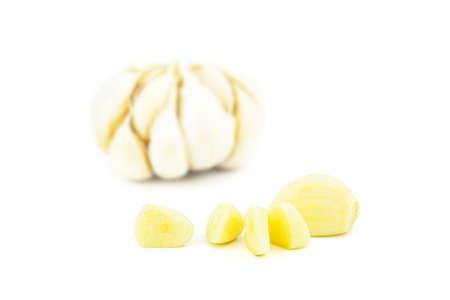 Chopped peeled garlic with blurred whole garlic isolated on white background