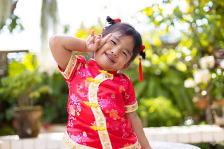Baby girl smiling in red Chinese outfit making I love you sign on blurred green garden background Stock fotó