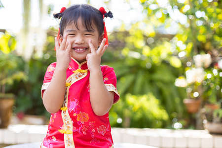 Baby girl smiling in red Chinese outfit to celebrate Chinese new year on blurred green garden background Stock fotó