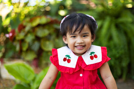 Cute asian baby girl smiling with happiness on blurred green garden background