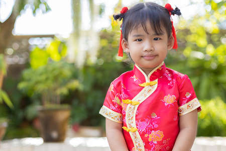 Baby girl in red Chinese outfit to celebrate Chinese new year on blurred green garden background