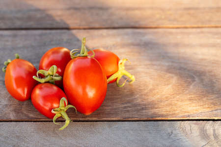 Fresh red tomatoes on vintage wooden table, selective focus