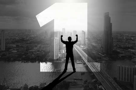 Double exposure silhouette of man standing inside number one with fists raising up over the city background, winning and achievement business concept