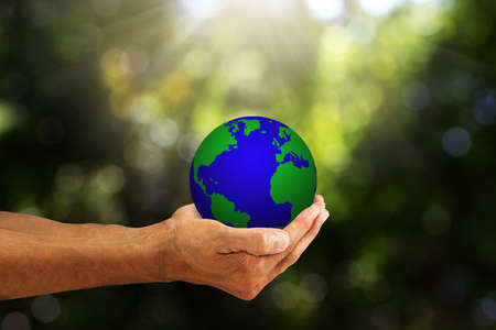 Hands holding planet earth on blurred green nature with sunlight background, environmental concept