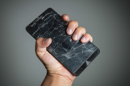 broken telephone: Cracked smart phone screen on hand.
