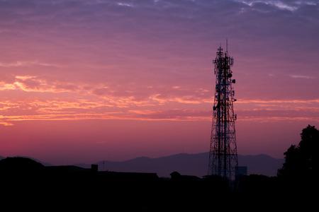 日の出や夕暮れの雲と空のシルエット通信塔。 写真素材