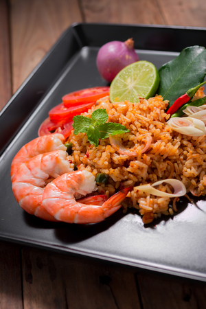 chinese meal: fried rice with shrimp, tom yum flavor, popular Thai food on wooden table. Stock Photo