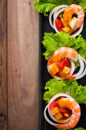 camaron: camarones agridulce, cóctel de gambas en el largo plato cuadrado y mesa de madera Foto de archivo