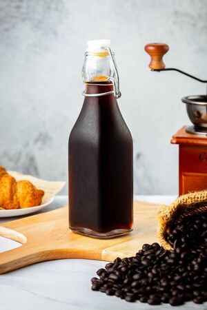Iced cold brew coffee in bottle on marble table decoration with coffee beans, croissant, grinder and rustic white background
