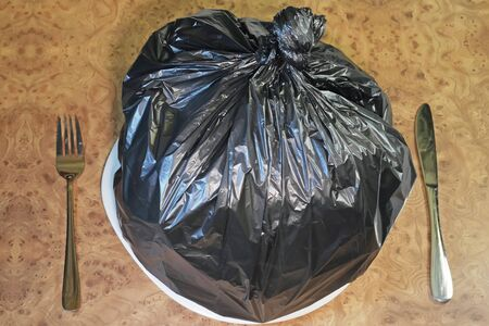 black plastic garbage bag: Food garbage and poor nutrition concept as a table setting with a black plastic garbage bag on a dinner plate with a knife and fork as a metaphor for a bad diet or doggy bag symbol.