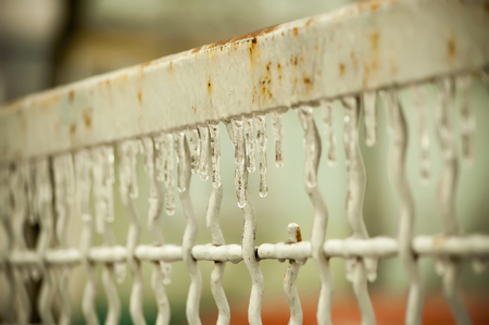 implications: rusty wrought iron fence covered in icicles