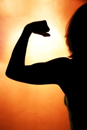 Silhouette of strong healthy woman flexing Stock Photo