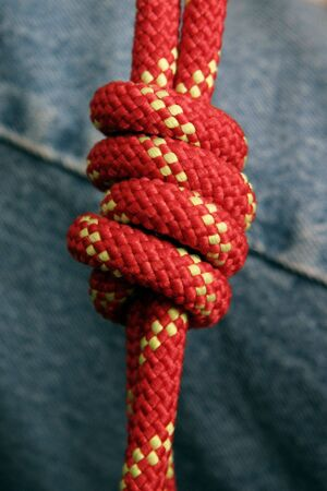 Red rope tied into a fishermans bend knot Stock Photo