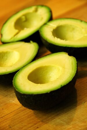 Two avocados cut in half, waiting for further prep.